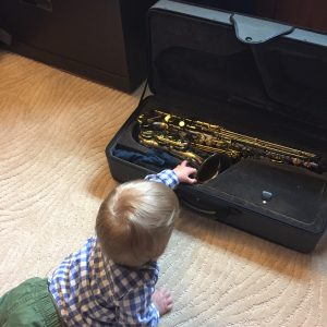 baby touching saxophone